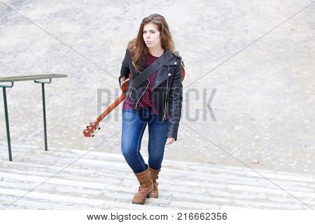 Portrait of serious young female musician walking upstairs in street and carrying guitar on back. Female guitar player going to work in bar or club. Creative work concept