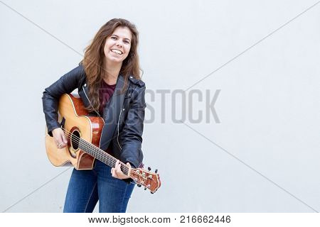 Cheerful young woman playing guitar and smiling at camera. Music and creative  concept.