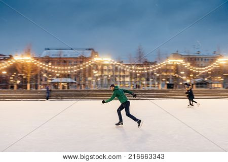 Young Male Begginer Learns Skating With Help Of Special Figure, Leans At It, Being On Ice Rink Cover