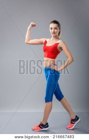 sport fitness woman flexing show her biceps muscles, young healthy smile girl athletic body, perfect figure in gym over grey background