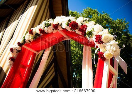 Arch for the wedding ceremony. Arch decorated with beautiful fresh flowers. Wedding arch of real flowers. Registration at the place of marriage.