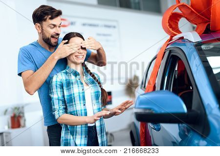 She is surprised at this. They are very happy about this, they are in a good mood. There are many modern cars.