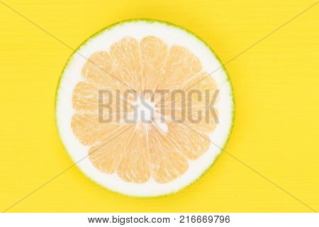 Sweetie fruit is cut into a round half on a yellow background