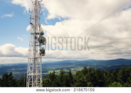 Aerials And Transmitters On Telecommunication Tower With Mountains In Background