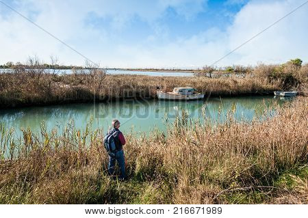 Hiker ( 60 Years Old) In Wild Area Of A Lagoon.