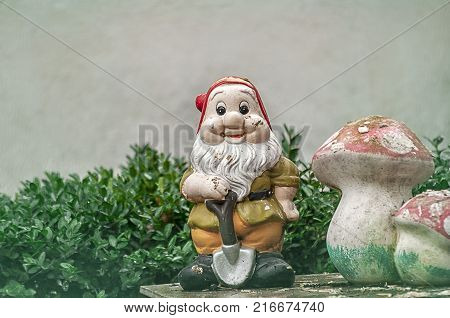 Garden gnome with a showel in hand close to a big mushroom