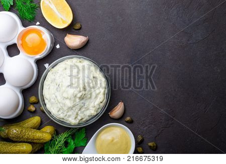 Homemade white sauce tartar tartare with ingredients pickles, capers, dill, parsley, garlic, lemon and mustard on a dark black stone concrete background. Horizontal, copy space, top view