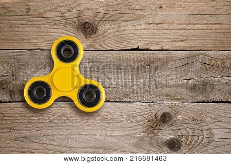 Fidget spinner toy on wooden table top view