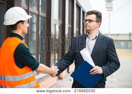 boss or Chief handshaking with workers engineers and giving salary in an envelope. Good job. Business modern background. poster