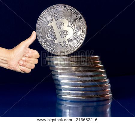 On a blue background are silver coins of a digital crypto currency Bitcoin. In addition to the lying coins there is standing bitcoin. The thumbs support a tilting group of coins - preventing the fall. Expand boom growth the value.