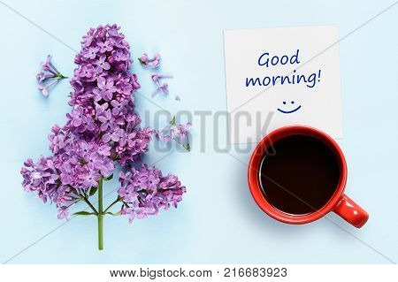 Good morning wishes coffee cup and lilac flowers on blue background top view