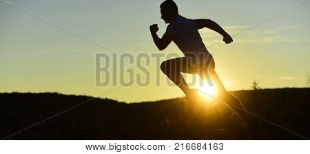 Silhouette of athlete running on sunset background copy space. Sportsman jogging in evening catching the sun. Man with sportive figure practices sport running for life. Sport and training concept.