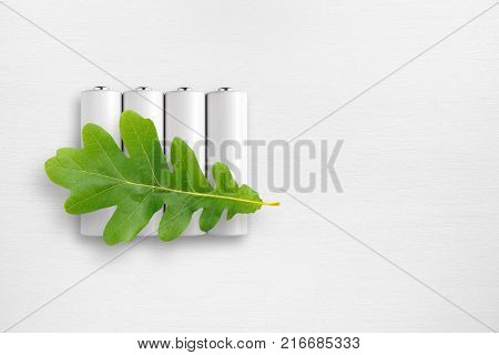 Batteries and green oak leaf on white table. Ecological energy concept.