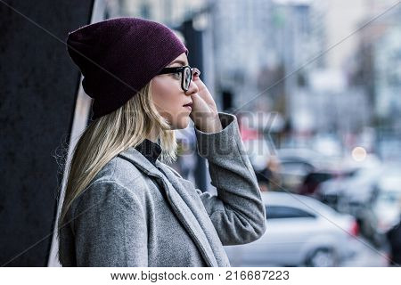 Confident and beautiful. Side view of attractive blonde woman holding glasses and looking away while standing outdoors. Stylish hipster girl walking autumn streets. City fashion concept.