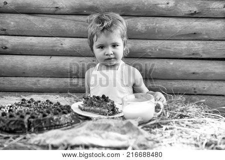 Cute little boy in white pinafore sits at table served with fruit cake and cup of milk outdoors on wooden background