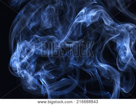 Blue smoke on black background. Abstract background with smoke. Spirit and ghost miracle. Smoking cloud backdrop. Blue ink in freeze motion powder splatted explosion.