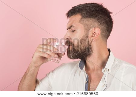 Hipster drink clean healthy water refreshing. Health and dieting. Life source and healthcare. Hangover and thirst. Man with long beard hold water glass on pink background. poster