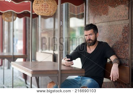 weblog and sms new technology and business bearded man with mobile phone sit in outdoor cafe