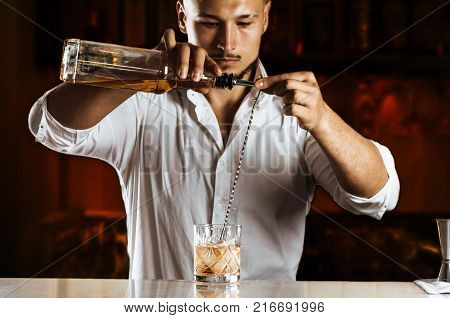 Charming Barman Elegantly Prepares A Mixed Drink By Pouring All The Ingredients Into A Bar Spoon.