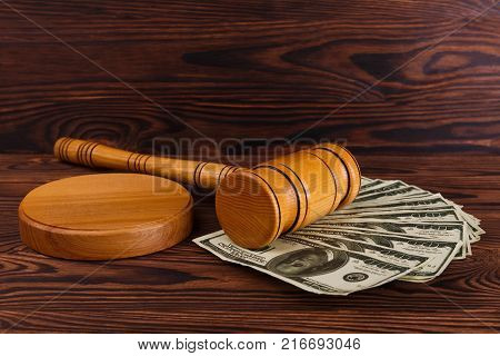 On the wooden table there are a bunch of dollar bills, a wooden auction hammer and a wooden stand. Auction. Side view.