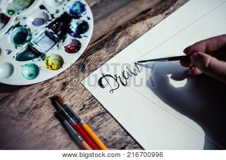 Closeup of  hand drawing letters. Artist durimg work process. Drawing process on wooden table with watercolor.