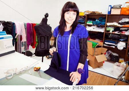 a female fashion designer is working on a new piece of clothing in her somewhat chaotic studio. in this shot, she is sewing textile pieces together and arranging them on a mannequin.
