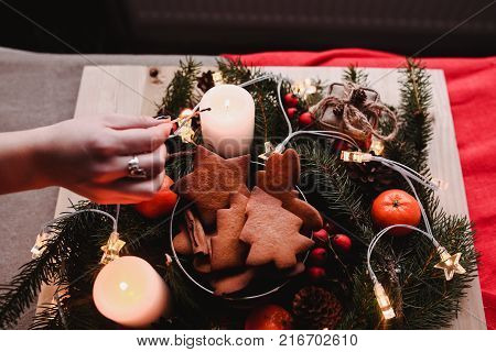 New Year's wreath with Gingerbread Cookies for xmas party. Woman's hand put cake on the top of bunch. Christmas eve.