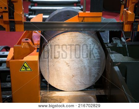 Band saw machine cutting metal work piece with coolant poster
