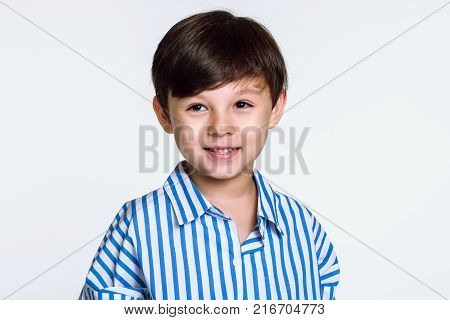 Studio portrait of a boy smiling happily looking to the side