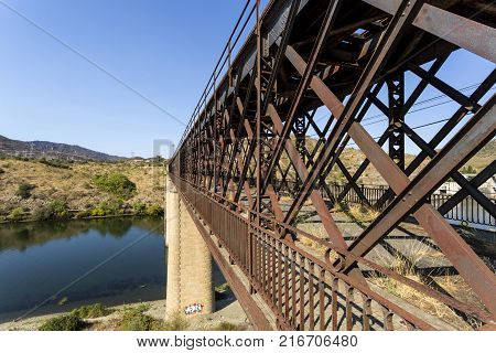 Abandoned truss road-rail bridge with the rail track above the roadway crossing the Douro River in Pocinho Douro region Portugal
