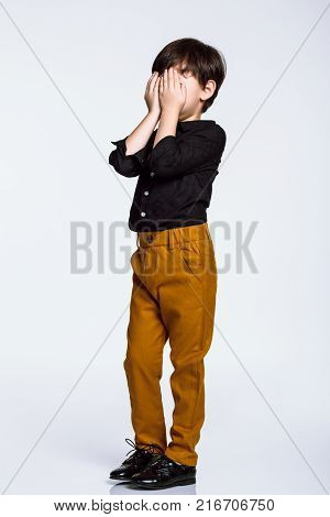 Full body portrait of a boy playing with hands on his face, casual dress