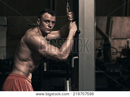 Fit strong athletic man using sport equipment in the gym, the image was desaturated ang toned