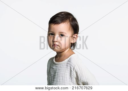 Studio portrait of a young girl staring at camera with sad eyes