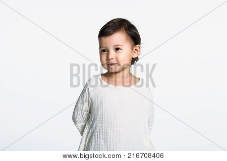 Studio portrait of a young girl looking sideways and having a happy look