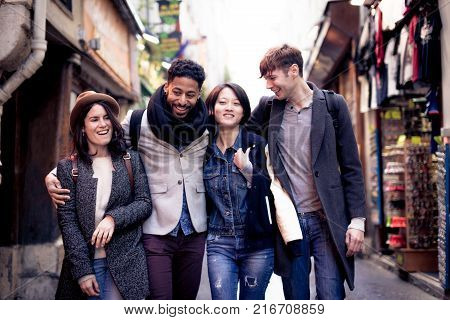 Multi-ethnic group of friends having fun in Paris, Latin Quarter, near Notre Dame Cathedral.