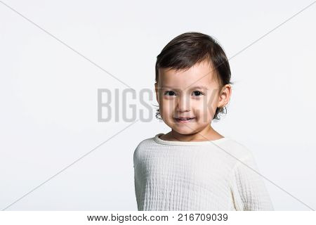 Studio portrait of a young girl staring at the camera and making a happy smile