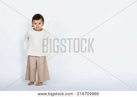 Studio full body portrait of a young girl hiding something back