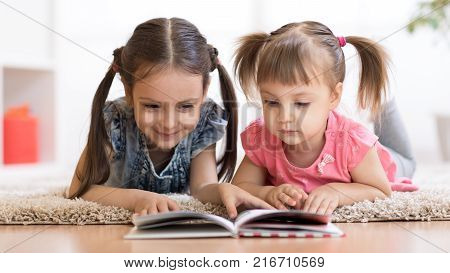 Child girl reading book with her little sister at home
