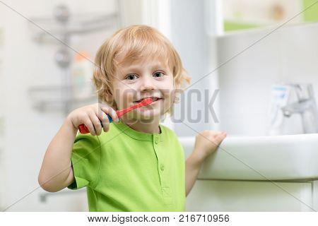 Happy kid or child boy brushing teeth in bathroom. Dental hygiene.