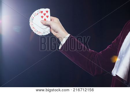 Midsection of magician showing fanned out cards against black background. Magician, Juggler man, Funny person, Black magic, Illusion.