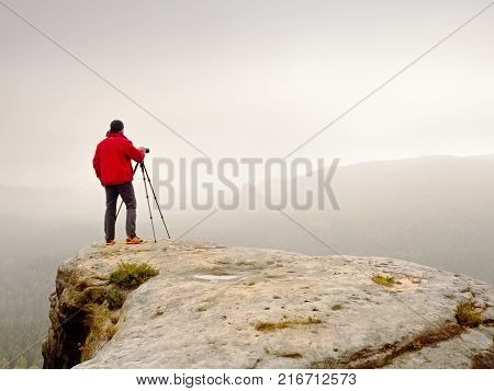 Male Legs In Dark Hiking Trousers And Leather Trekking Shoes On Peak Of Rock Above  Misty Valley. Ou