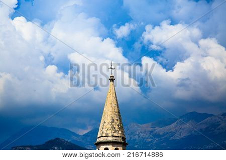 Spire of medieval catholic cathedral on background of stormy sky, dramatic clouds and mountain ranges. Saint Ivan Church in old town of Budva, Montenegro.