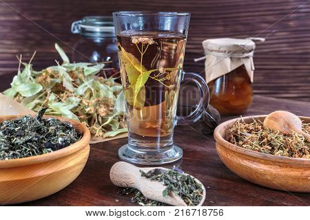 linden tea on a background of dried lime flowers, lemon balm and St. John's wort