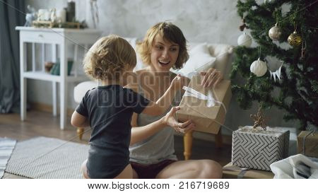 Happy mother and her little beautiful unpack gift box near the Christmas tree at home