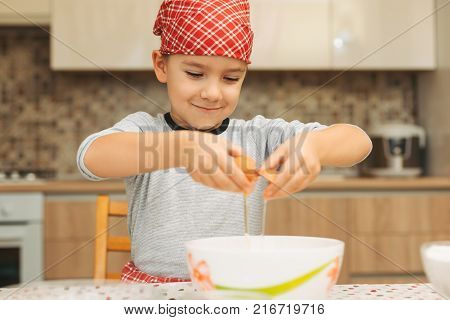 Little boy cooking. Child breaking egg into bowl. Happy childhood. Boy kid baking preparing biscuits. Kitchen. Real. Processes.