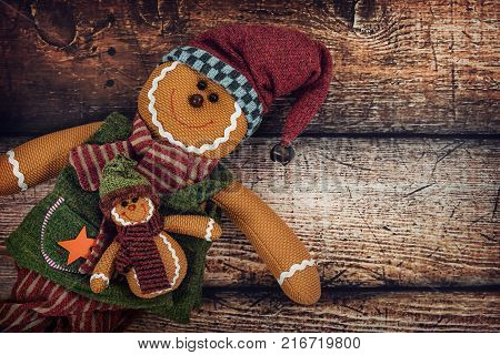Cute decorative craft gingerbread man dolls against vintage wooden background