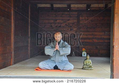 Buddhist Meditation. Older man meditating  in a wooden house. Senior man practicing meditation with a Buddha Statue.