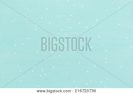 turquoise wooden background with small shinny silver stars