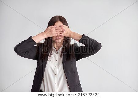 woman in a suit, blocking her eyes, business compliance concept.
