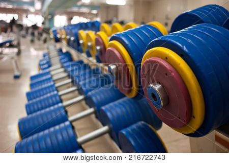 dumbbells with yellow and red cargo disks in the gym, lie in a row. background